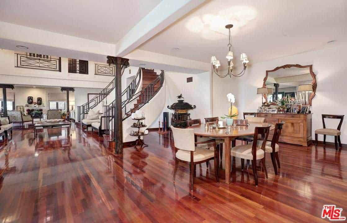 This great room that has a sleek redwood flooring and white ceiling houses the living room as well. The dining room area has wooden chairs with beige cushions and redwood frames that blend well with the flooring.