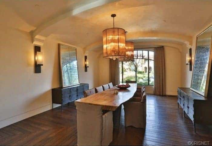 The pendant lights hanging from the cove ceiling augment the white elements with their warm glow of yellow lights. This is then contrasted by the dark hardwood flooring that matches the dark wooden cabinets and the dark brown slipcovers of the chairs.