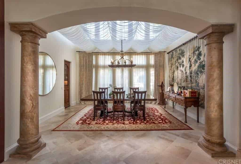 The arched entryway to this dining room is guarded by two thick columns with a brass-like hue that complements the beige marble flooring well as the wooden elements of the dining set and the console table that is adorned with a large tapestry of a tree.