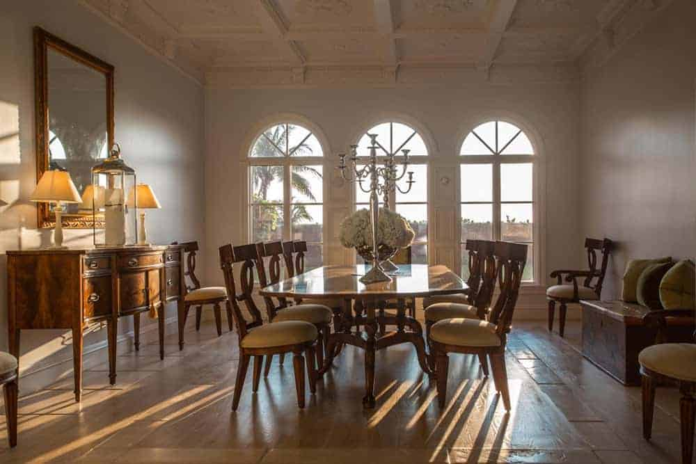 The far wall of this spacious and airy Mediterranean-style dining room has three arched windows that bring in an abundance of natural lighting to the wooden dining set with beige cushions that match the beige marble flooring.