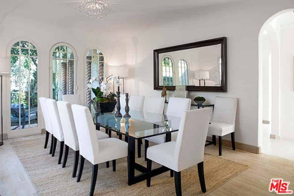 This bright dining room has a white ceiling with a decorative lighting, white walls with a large wall-mounted mirror and white cushioned chairs that are paired with a long rectangular glass-top dining table over a woven area rug.
