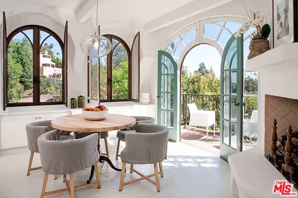 This charming dining room is adorned with arched windows and arched glass doors that lead to a balcony. The charm of this dining room is augmented by a fireplace with a white mantle that blends with the flooring making the gray cushioned chairs and wooden dining table stand out.