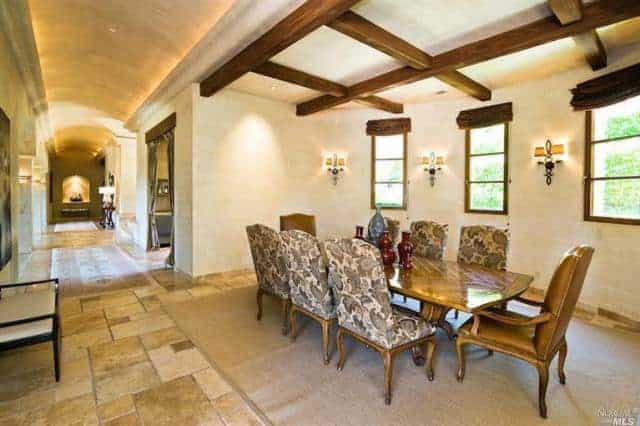 This dining area is by the hallway that has a cove ceiling. This differs with the ceiling of the dining area that has exposed wooden beams matching the wooden dining table that is surrounded by chic chairs illuminated by charming wall lamps.