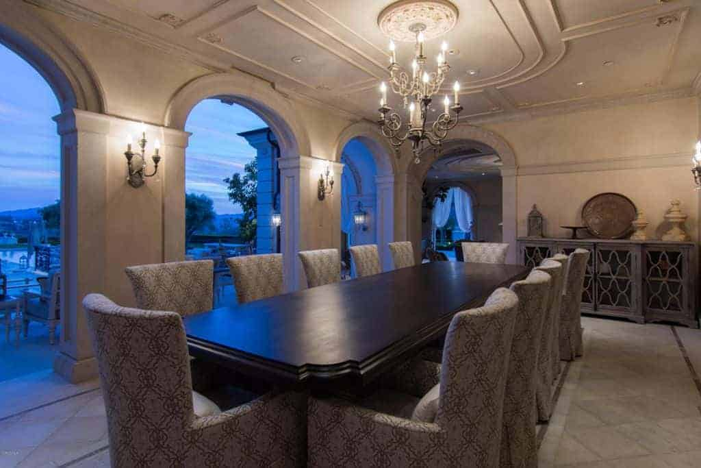 The large dark rectangular dining table is complemented by its dining chairs that has gray cushions with subtle elegant patterns to it. This is augmented by the two-tier chandelier that matches well with the wall lamps.