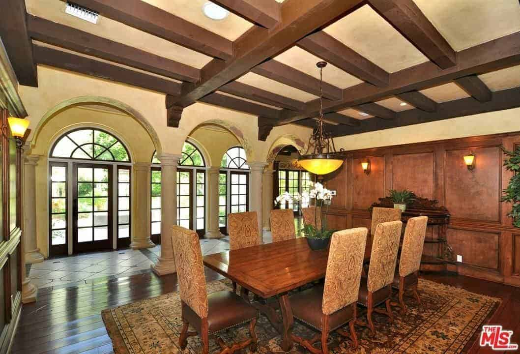 This dining room has chocolate brown exposed wooden beams on its beige ceiling. This is complemented by the brown wooden finish of the walls and the dark hardwood flooring. These are a nice background for the wooden dining table and its floral cushioned chairs.