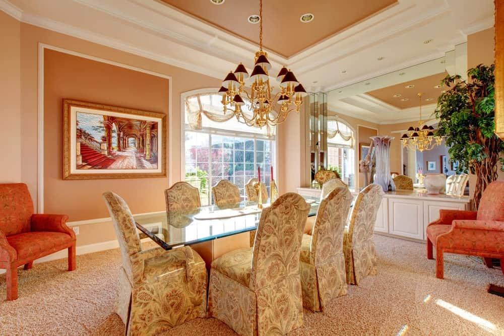 The light pink carpeted flooring of this formal dining room matches with the walls that are adorned with a colorful painting and an arched window. It also matches the ceiling that hangs a chandelier over the glass-top dining table that is surrounded by chairs with floral slipcovers.