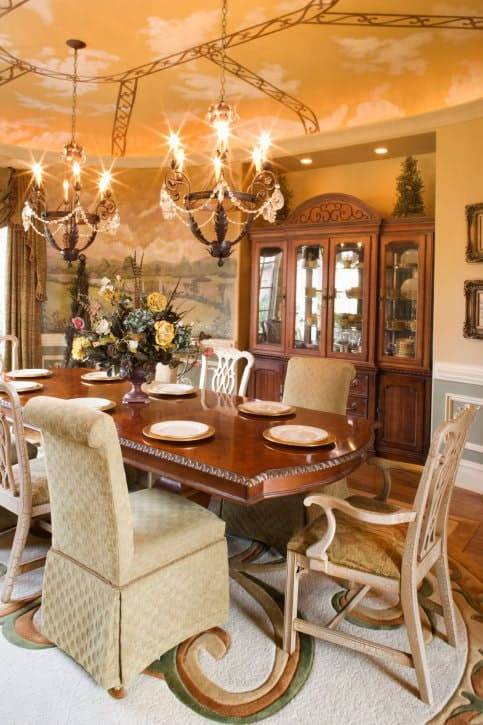 This elegant and charming dining room has a ceiling painted with a sunset sky augmented by the warm yellow lights of the chandeliers. These pair well with the large wooden dining table over the elegant area rug with intricate patterns.