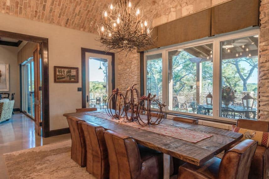 The highlight of this Mediterranean-style dining room is the unique chandelier that has a peculiar bird's nest design that goes well with the decors on the rustic wooden dining table paired with brown leather chairs and brown area rug.