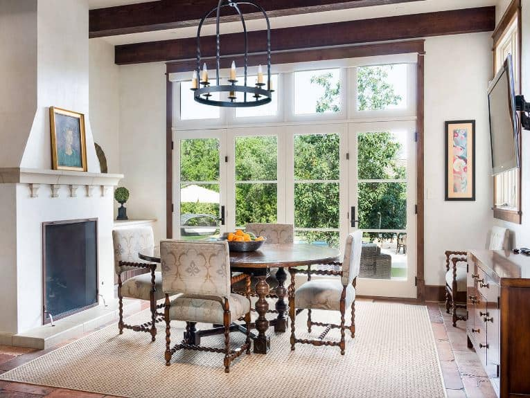 The chandelier has a birdcage design that matches with the wooden leg designs of the cushioned chairs. These go well with the circular wooden dining table that stands out against the woven area rug over the terracotta flooring.