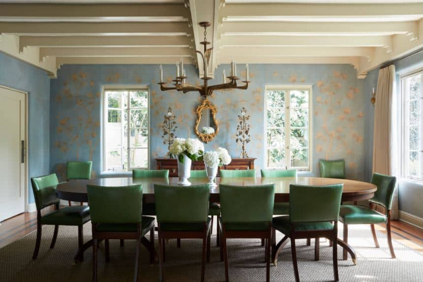The green leather cushions of the dining chairs surrounding the large wooden dining table is a great complement to the light blue wallpaper of the dining room that has subtle floral elements to it adorned with an elegant mirror.