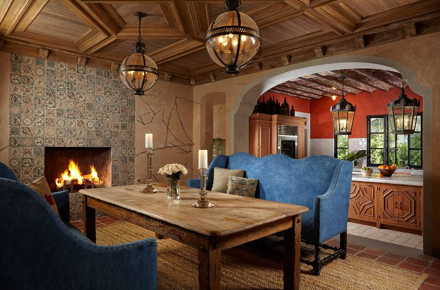 This charming and warm Mediterranean-style dining room has a couple of cushioned couches paired with a rustic wooden dining table. This is topped with a coffered ceiling and two spherical pendant lights that augment the fireplace inlaid with patterned tiles.