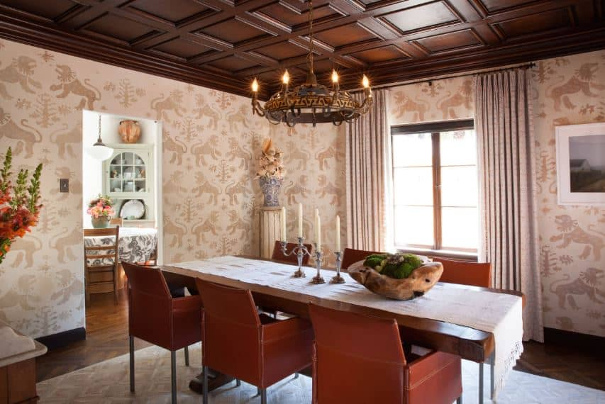 The walls of this Mediterranean-style dining room are dominated with a wallpaper that has patterns of lions. This wallpaper matches with the area rug underneath the dark brown leather chairs that matches the dark brown coffered ceiling.