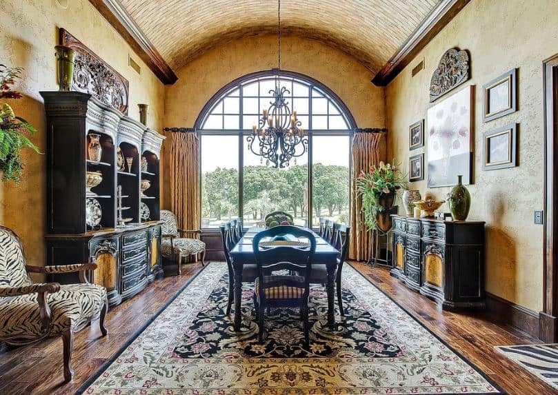 The high ceiling has a cove finish accented with a wrought iron intricate chandelier. The intricacy of this chandelier matches the colorful patterned area rug underneath the long dark wooden table paired with dark wooden chairs.