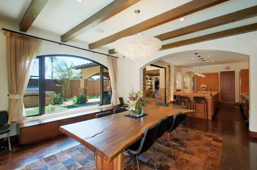 A majestic crystal decorative lighting hangs over the rustic wooden table. This table has a dark wooden hue that matches the hardwood flooring topped with a similar hued patterned area rug. All of these are illuminated by the wide arched glass window.