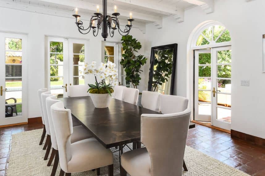 The wrought iron intricate chandelier stands out against the white ceiling that has exposed wooden white beams. This ceiling is contrasted by a terracotta flooring topped with a woven area rug that goes well with the cushioned wing back dining chairs.