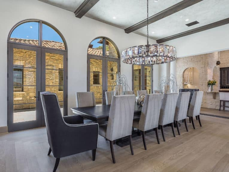 The light gray ceiling of this formal dining room has dark wooden exposed beams that pair well with the dark wooden dining table. This stands out against the light hardwood flooring and the light gray dining chairs topped with a large circular decorative chandelier.