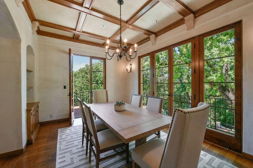 The light gray upholstery of the dining chairs are lined with studs and have wooden frames that match the wooden dining table. This setup is surrounded by beige walls and ceiling that are accented with wooden beams and frames that match the hardwood flooring.