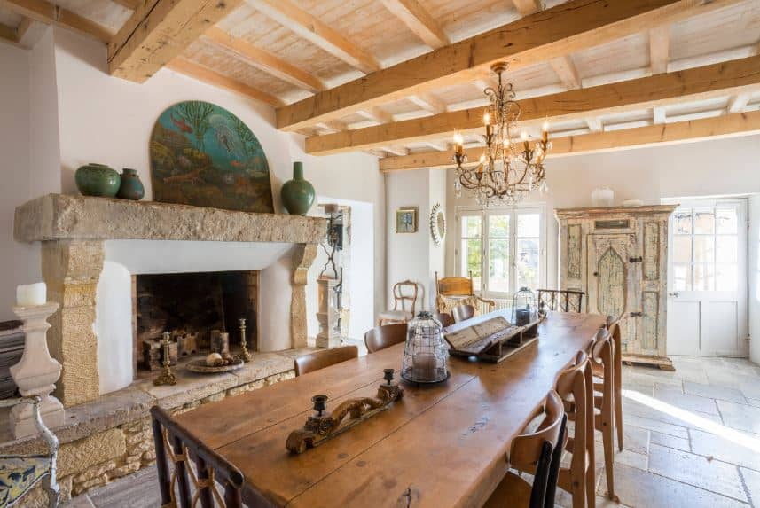 The wooden ceiling of this dining room is dominated by large exposed wooden beams that support a chandelier over the rustic wooden table warmed by a fireplace that has a beige stone mantle that supports a colorful painting above.
