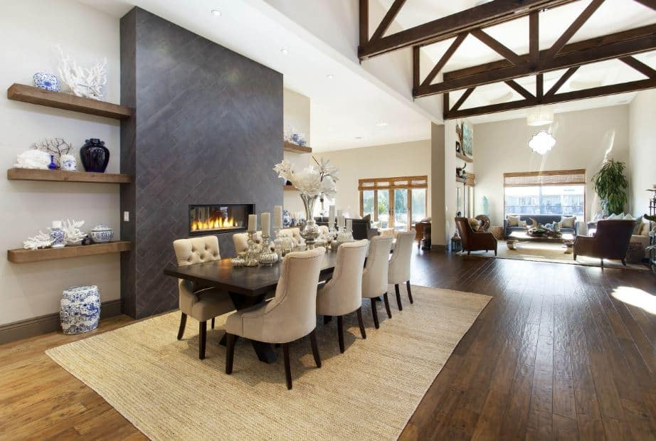 The white wall beside the long dining table is dominated by a large dark gray stone structure that houses the modern fireplace and shelves on each side bearing decors. These wooden shelves match with the hardwood flooring that is topped with a rustic woven area rug.