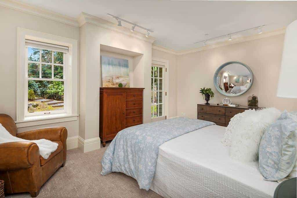 Airy bedroom decorated with a round concave mirror and lovely artwork illuminated by white track lights. It has a brown leather armchair and a comfy bed filled with fluffy and furry pillows.