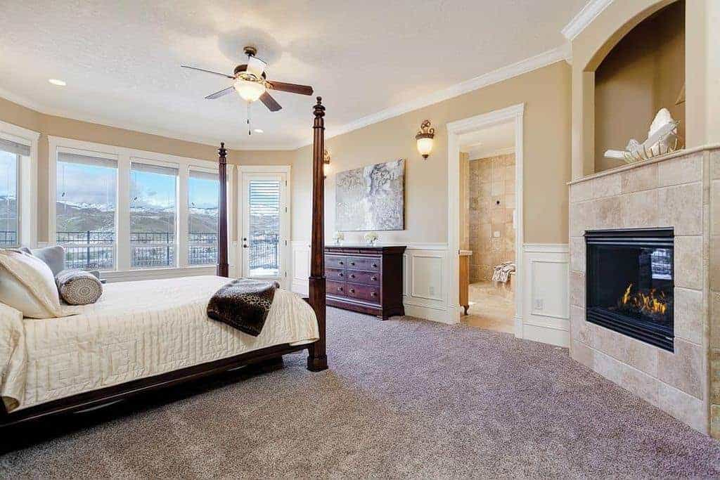 Sophisticated master bedroom with carpet flooring and glass paneled windows inviting natural light in. It includes a modern fireplace and four poster bed that complements the wooden dresser.