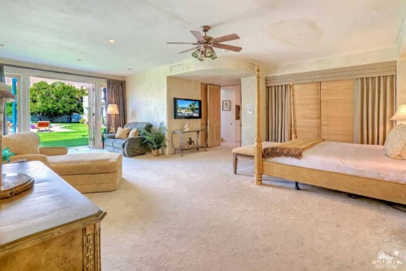 A four poster bed faces the glass top console table and wall mount TV in this beige master bedroom with carpet flooring and glass double door that leads out to the lush green yard.