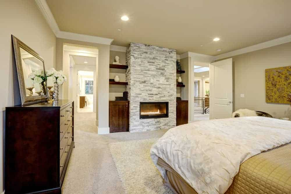 This master bedroom showcases a comfy bed and glass enclosed fireplace fitted on the brick pillar. It includes built-in shelving and dark wood dresser topped with mirror and glass flower vase.