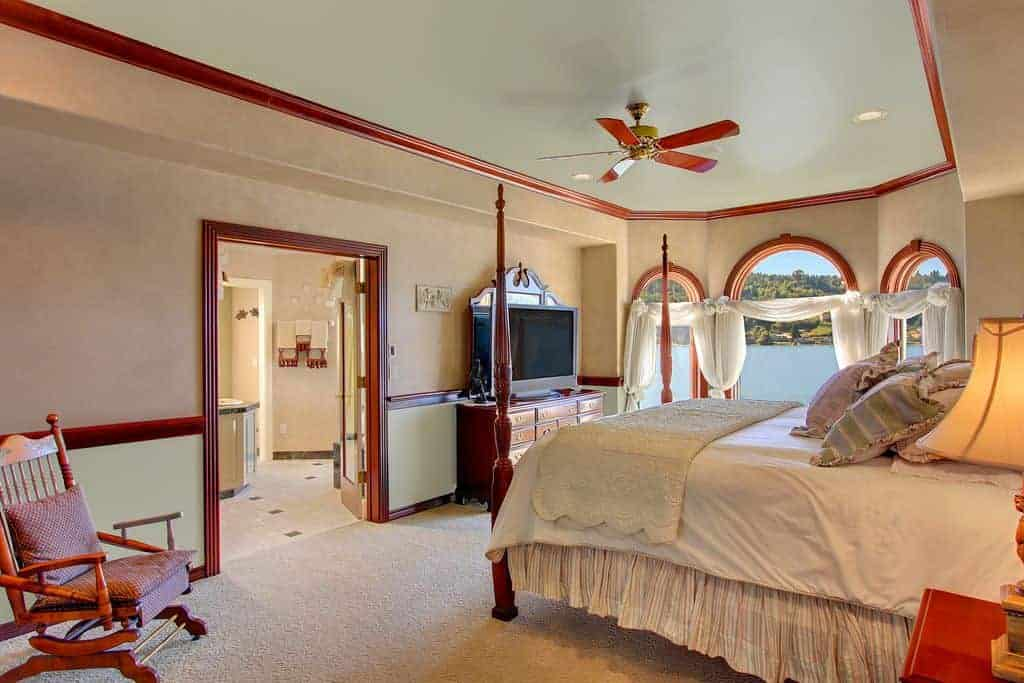 Beige master bedroom lined with redwood moldings that complement the four poster bed, dresser and wooden armchair. It has a ceiling fan and arched windows dressed in white sheer curtains.