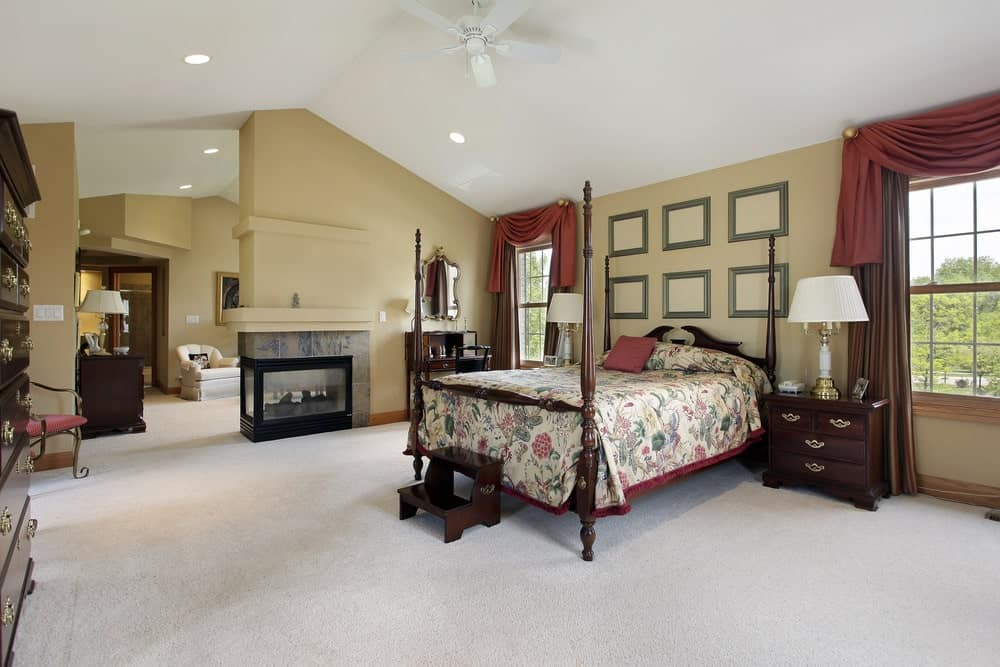 A large master bedroom with carpet flooring and wooden framed windows dressed in brown drapes and red valances. It includes a four poster bed and a seating area behind the triple sided fireplace.