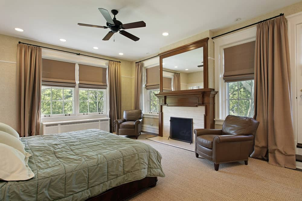 Beige bedroom with a comfy bed wrapped in a sage green duvet that faces the fireplace flanked by white framed windows and brown leather armchairs.