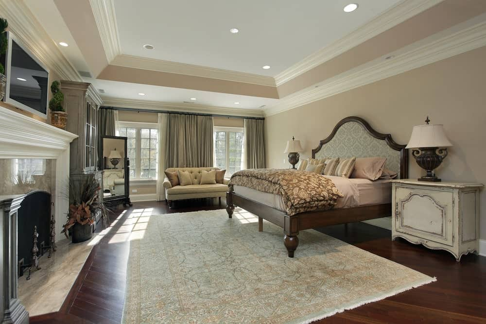 Natural light streams in through the white framed windows in this master bedroom with a marble fireplace and wooden bed situated in between distressed nightstands.