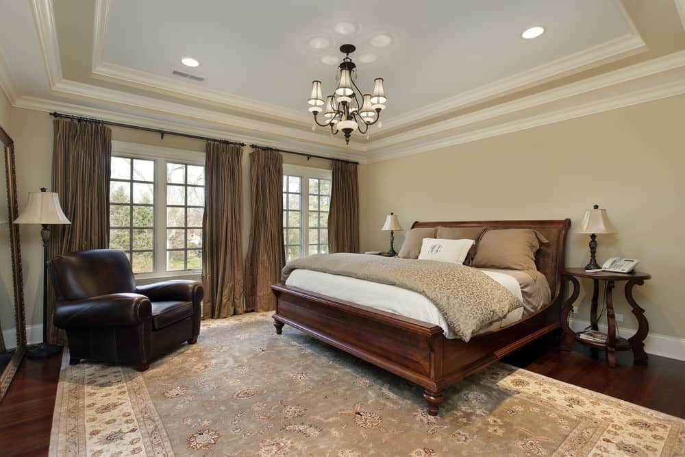 A gorgeous chandelier illuminates this classic beige bedroom offering a wooden bed and leather armchair over a floral area rug.