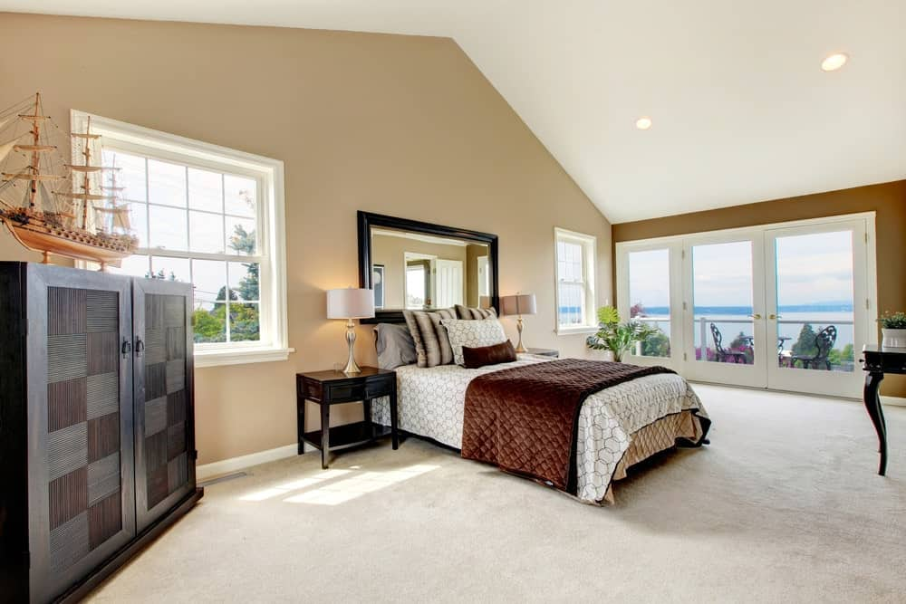 Spacious bedroom with cathedral ceiling and a French door that opens to the balcony with an amazing outdoor view. It includes a cozy bed and wooden cabinet topped with a ship decor.