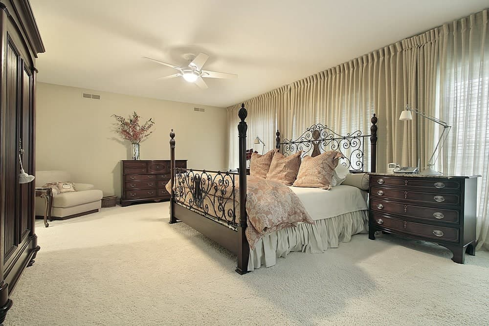 Dark wood nightstands complement the wardrobe and dresser that's topped with a chrome flower vase. This room features an ornate four poster bed accented with floral pillows and duvet.