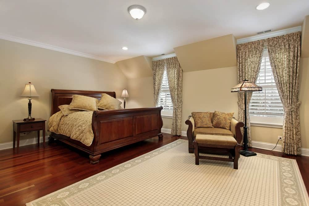 The classic master bedroom offers a wooden bed and round back lounge chair lighted by a charming floor lamp. It has a bordered area rug and patterned drapes covering the glazed windows.