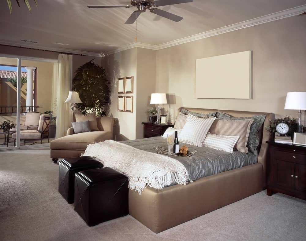 Beige master bedroom with dark wood nightstands and upholstered bed accompanied by a matching chaise lounge and black ottomans.