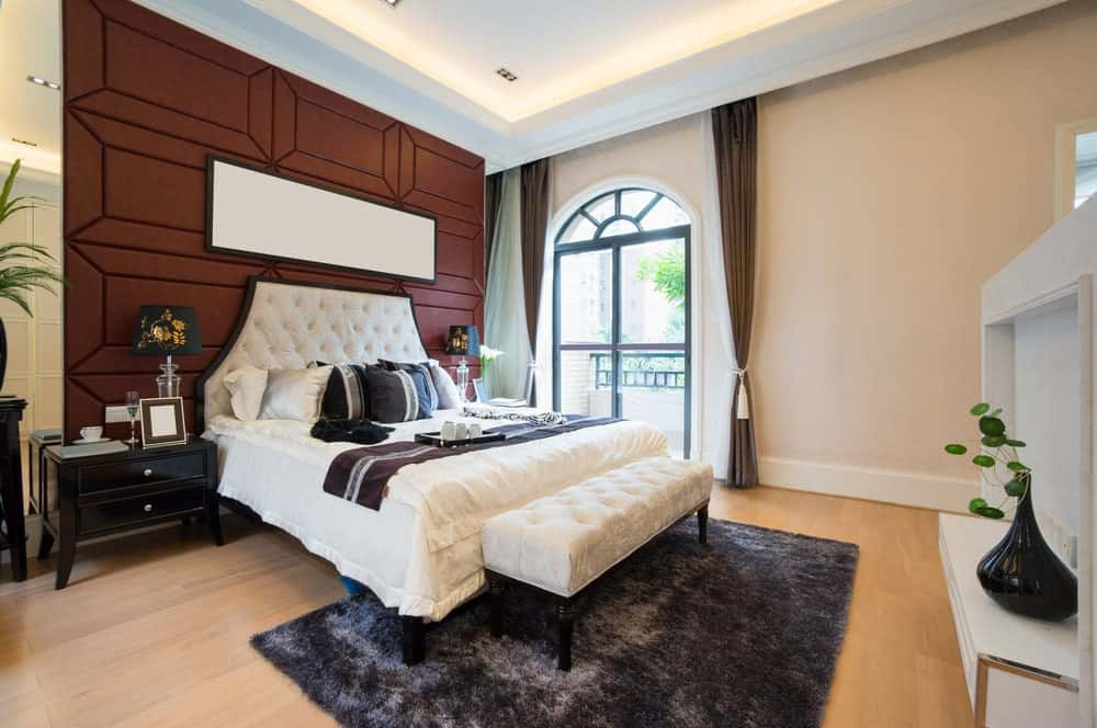 Elegant master bedroom with paneled accent wall and arched window allowing natural light in. It has dark wood nightstands and white tufted bed with a matching bench on its end over a gray shaggy rug.
