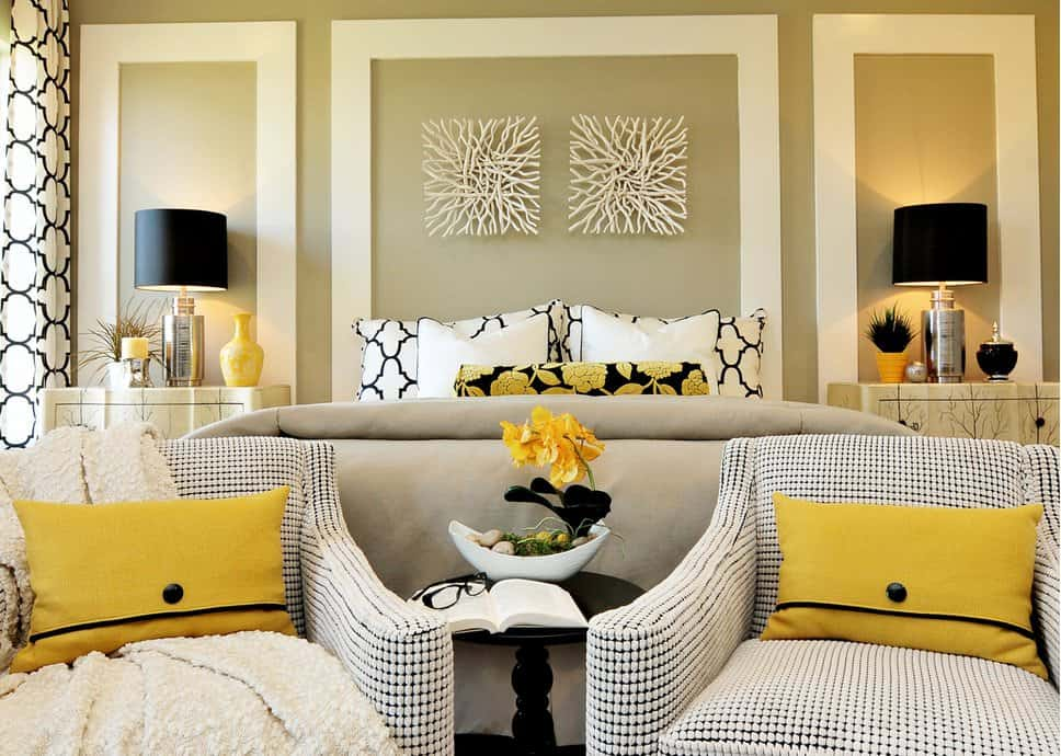 A pair of driftwood wall arts hang above the bed in this fabulous master bedroom with black table lamps and patterned armchairs accented with yellow pillows.