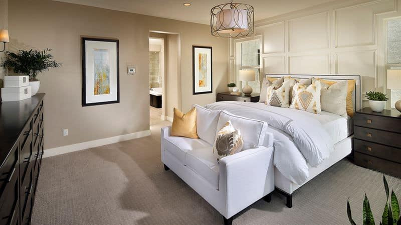 A stylish drum pendant light illuminates this beige master bedroom boasting white bed and loveseat contrasted by darkwood nightstands and dresser.