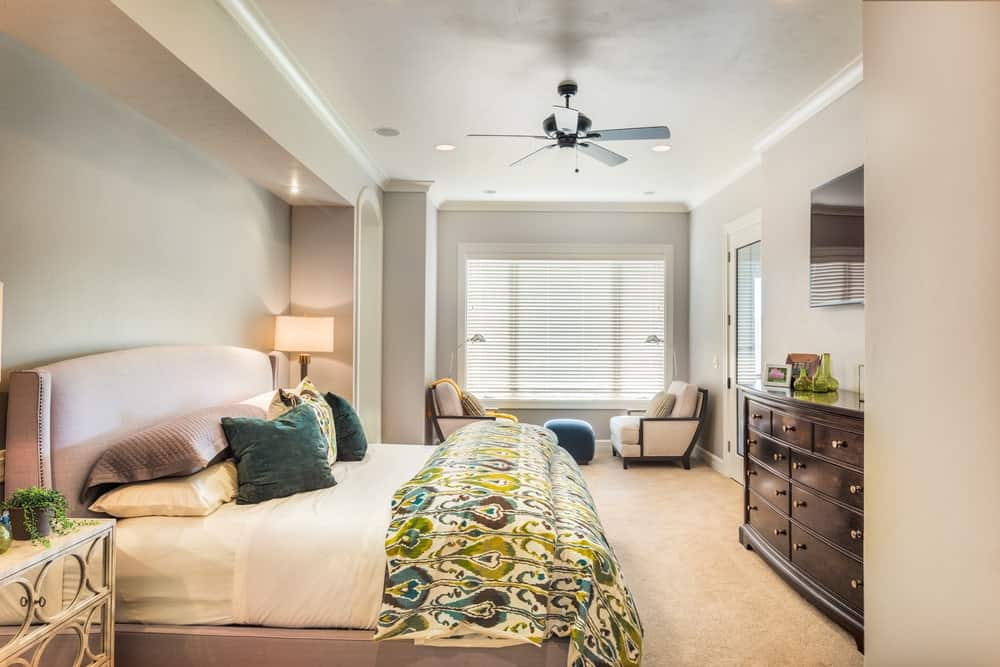Fresh master bedroom showcases a seating area and an upholstered bed facing the wooden dresser and frameless mirror. It has carpet flooring and regular ceiling mounted with fan and recessed lights.