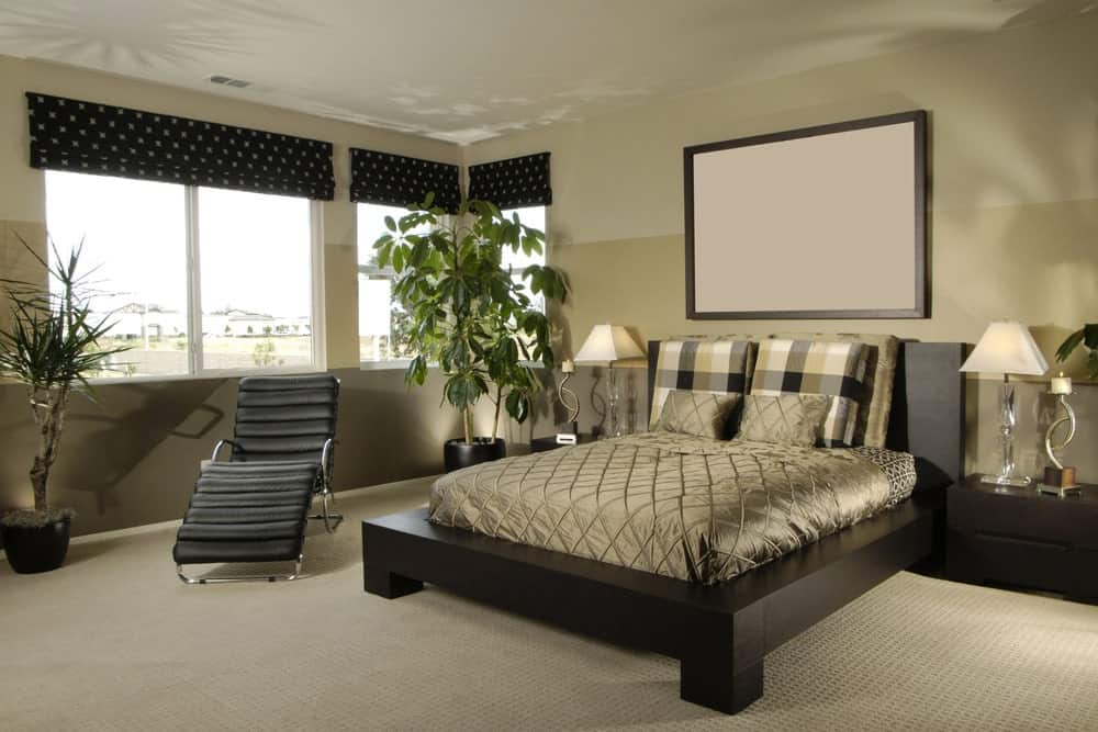 Fresh master bedroom with three-tone walls and glazed windows covered in black dotted roman shades. It includes a black lounge chair and platform bed lighted by glass table lamps.