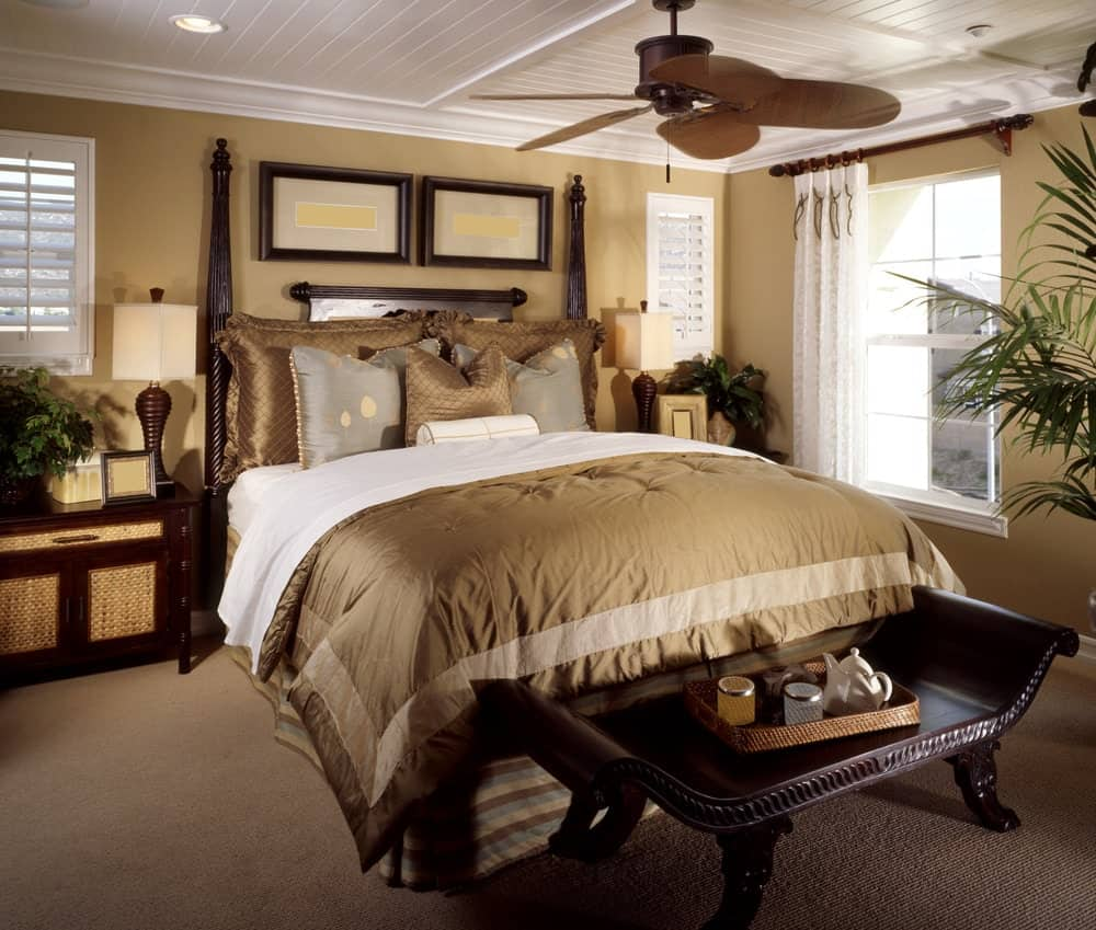 Tropical master bedroom boasts a classy bed and bench over carpet flooring. It includes a ceiling fan and wooden nightstands topped with sleek table lamps.