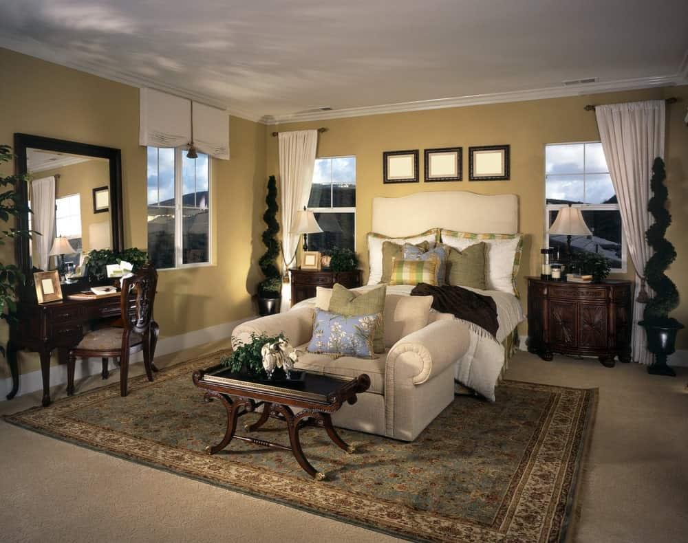 Carved wood nightstands flank a beige bed with a loveseat on its end paired with a dark wood coffee table. This room has a vanity and classic area rug that lays on the carpet flooring.