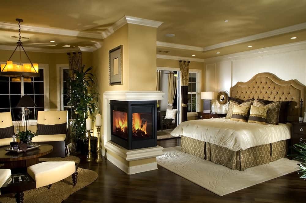 Warm master bedroom with cozy rugs and triple sided fireplace that serves as a divider to the tufted bed and seating area. It is illuminated by a vintage chandelier and recessed ceiling lights.