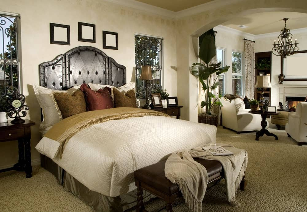 A brown leather bench sits in front of the skirted bed in this master bedroom offering a seating area by the fireplace lighted by a traditional floor lamp and an ornate chandelier.