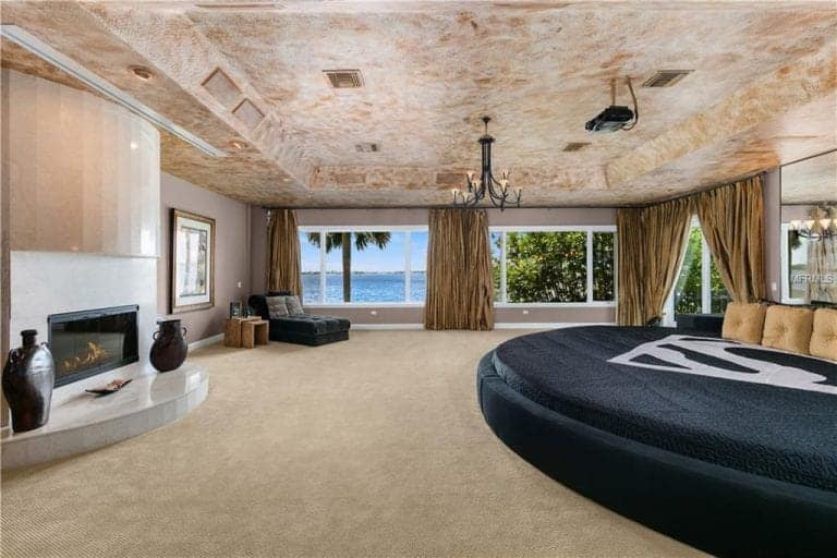 The spacious master bedroom features a modern fireplace and a large round bed with a frameless mirror on top. It has a tray ceiling and glass paneled windows that overlook a stunning ocean view.