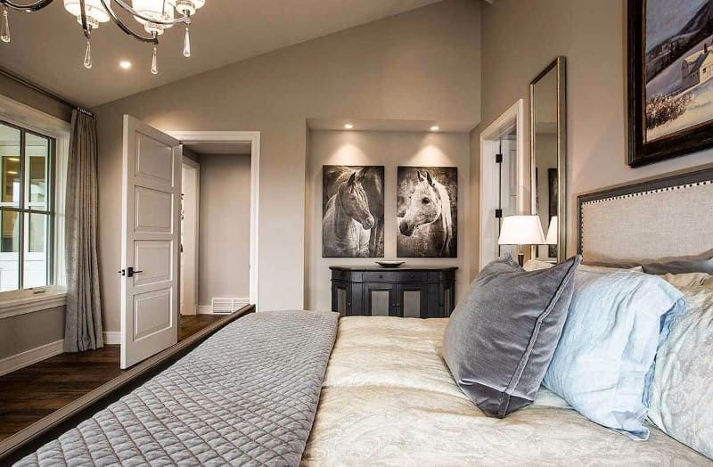 The classy master bedroom features a cozy bed lined with a gray quilt. There's a dark wood console table on the side that's accented with horse paintings mounted on the inset wall.