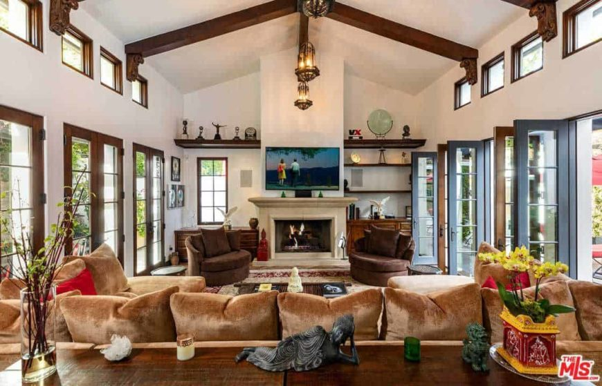 This living room offers a nice and classy brown couch along with a pair of brown seats near the fireplace. The area has a tall ceiling with exposed beams.