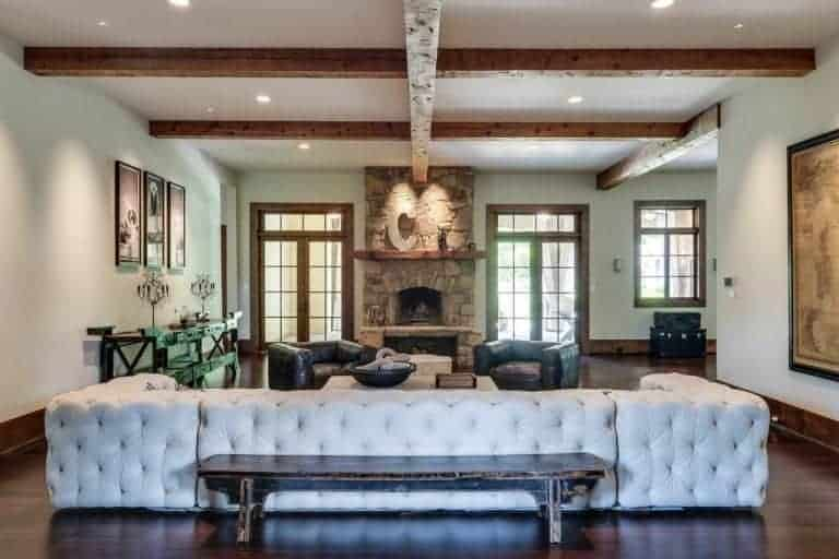 Large living room boasting an large elegant couch and a pair of leather seats, along with a fireplace.