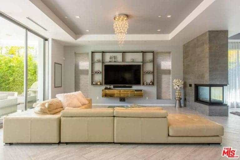 A gorgeous and modern living room featuring hardwood flooring and a tray ceiling lighted by a glamorous ceiling light. The area offers a large sofa set along with a large widescreen TV on the wall, surrounded by built-in shelves.